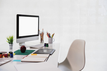 Stylish workspace with desktop computer, office supplies, houseplant and books at home or studio. Blank screen for graphics display montage.
