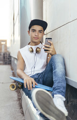 Young man looking at smartphone with skateboard and headphones