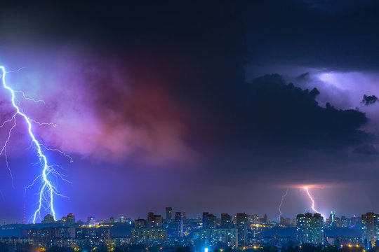 Lightning over the city at the summer storm. Dramatic, breathtaking atmospheric natural phenomenon.