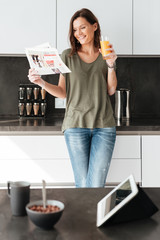Vertical image of smiling casual woman reading newspaper