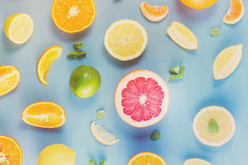citrus food pattern on blue background - assorted sliced citrus fruits with mint leaves, retro toned