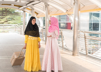 Arab traveler woman greeting friend while walking carrying a suitcase