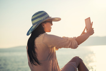 Smiling young woman take a selfie photo with digital tablet on the sea