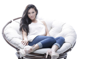 Modern young woman sitting in a round cozy soft chair