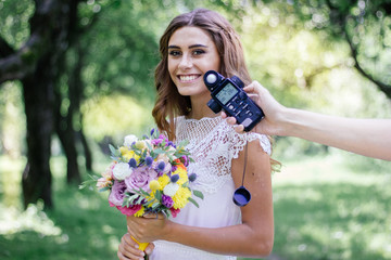 Photographer measuring light with light meter on beautiful girl