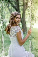 Beautiful bride with nice wedding hair style on swing.