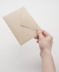 Female hand holding craft envelope, isolated on white