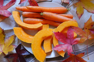 Pumpkin and carrot Slices. Fresh autumn vegetables. Composition of pumpkin and carrot on the wooden cut board. Autumn food composition with yellow leaf. Happy Thanksgiving composition.