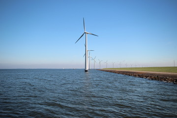 Windmills along the shore of a big lake in the Netherlands
