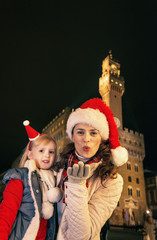 mother and child in Christmas hats in Florence blowing air kiss