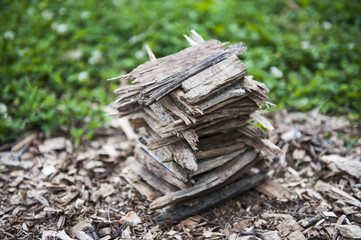 Stack of wood chips next to grass.