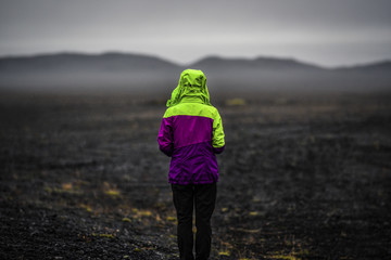 Woman looking on a Iceland landscape, black volcanic dust and mountains with fog in background.