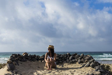 young beautiful woman sitting on the sand surrounded of volcanic black rocks. Sea background. Horizon Canary islands