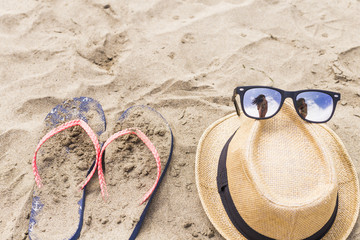 Beach accessories, summer outfit. flip flop, hat and sunglasses with a selfie reflection. Lifestyle. Beach