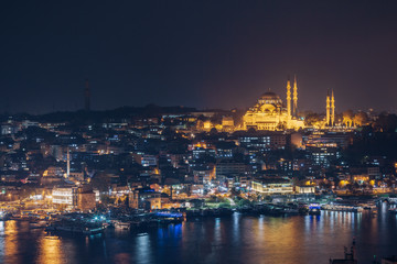 Istanbul sunset panorama - Turkey travel background. Night view on the restaurants at the end of the Galata bridge, Sultanahmet, at sunset with the famous Suleymaniye Mosque in the background