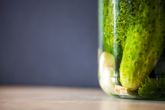 Pickled cucumbers in a jar with spices and herbs copy space