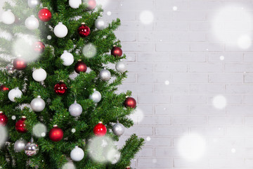 christmas tree with colorful balls over white brick wall and snow