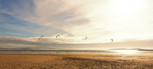 Kite surfers glide on the waves of the Atlantic ocean.Active leisure concept. Panoramic landscape