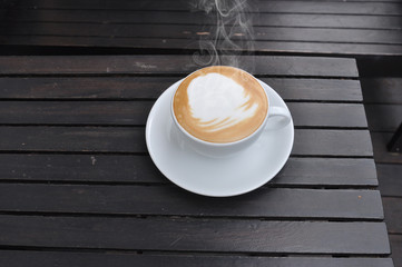 white cup of hot coffee on wooden table in coffee shop,
