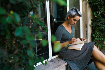 Woman reading book at window