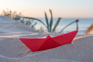 Red paper boat on a beach