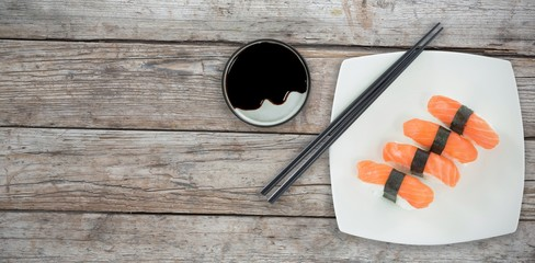 Composite image of high angle view of chopstick by salmon sushi