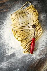 Homemade italian tagliatelle with flour. Dark background.
