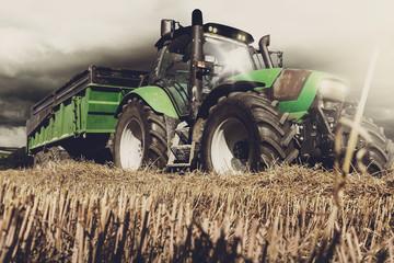 tracteur et sa remorque sous un ciel d'orage