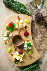Close-up of a cheese plate. 4 types of cheese, soft white brie cheese, camembert, semi-soft briques, blue, roquefort, hard cheese. Walnuts, green grapes, sauce, white wine. Beautiful serve, top view