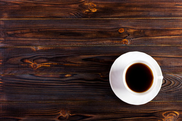 Coffee cup on wood texture and background with space.