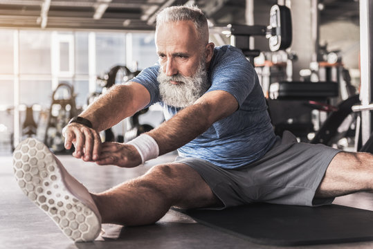 Serious old bearded man is enjoying exercises in fitness center
