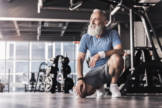 Joyful old male is spending time in modern gym