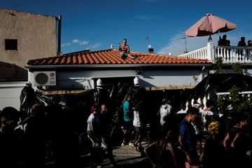 A man sits on a roof as he takes pictures of revellers covered in grease taking part in the annual Cascamorras festival in Baza, southern Spain