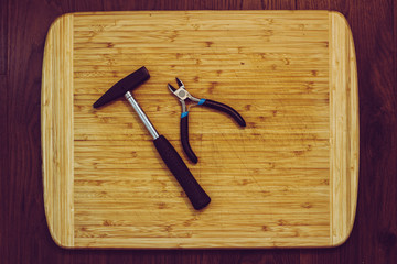 wooden kitchen cutting board with hammer and tools