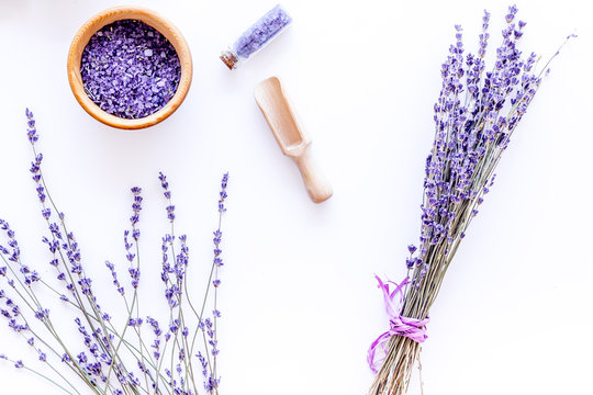 bath salt in herbal cosmetic with lavender on white desk background top view
