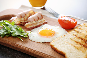 Tasty breakfast with egg on wooden board