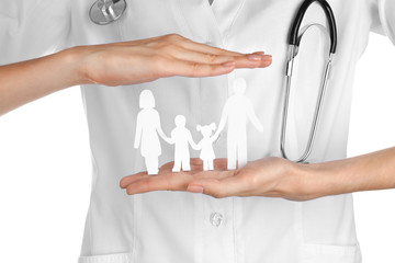 Female doctor holding paper silhouette of family on white background. Health insurance concept