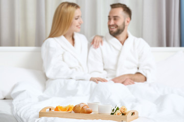 Tray with breakfast in hotel room and happy young couple on background