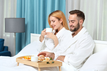 Young couple having breakfast in hotel room