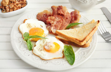 Tasty breakfast with fried eggs and bacon on table