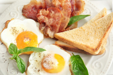 Tasty breakfast with fried eggs and bacon, close up