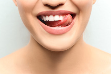 Young smiling woman licking her teeth on light background, closeup