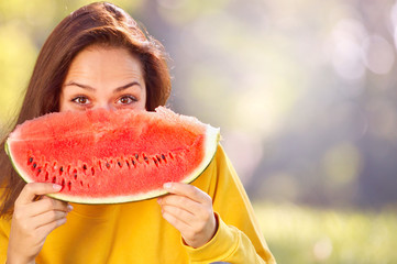 Happy young woman eating watermelon in the park