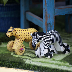 Wooden toys: a tiger and a zebra on wheels in the window of a toy store for children