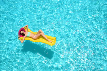 Beautiful young girl relaxing on inflatable mattress in blue swimming pool