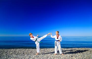 Тренировка двух детей на пляже, на море: тхэквондо, спорт