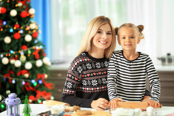 Young woman preparing Christmas cookies with little daughter in kitchen