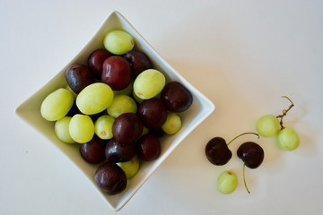 Tasty cherries and grapes in the white square plate on the white table