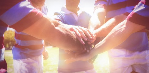 Rugby team stacking hands