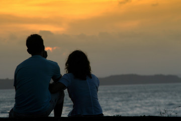 Romantic couple on the beach in Brazil at colorful sunset on background